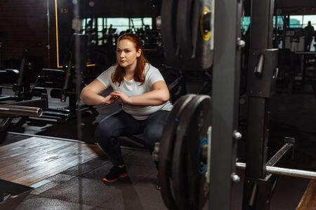 focused overweight girl squatting with clenched hands near fitness machine