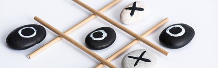 panoramic shot of tic tac toe game with grid made of paper tubes, and pebbles marked with naughts and crosses on white surface