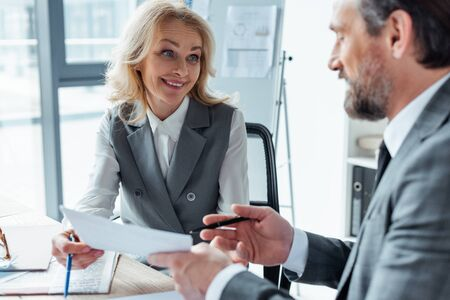 Selective focus of smiling businesswoman holding document near businessman at table in office