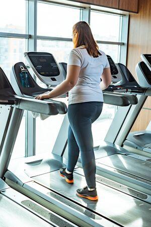 redhead overweight girl training on treadmill in gym near window