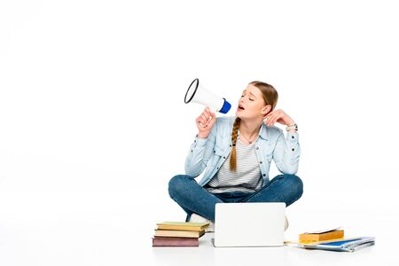 girl sitting on floor with loudspeaker near laptop, books and copybooks isolated on white