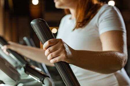 cropped view of overweight girl working out on stepper in gym Stock Photo