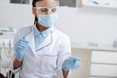 african american dentist in medical mask, face shield and latex gloves pointing with finger in clinic