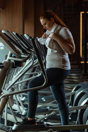 side view of focused overweight girl training on stepper while holding towel