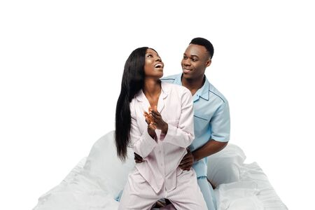 happy african american couple sitting in bed in pajamas isolated on white