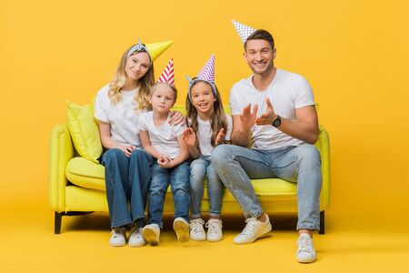 happy family in birthday party caps applauding on sofa on yellow
