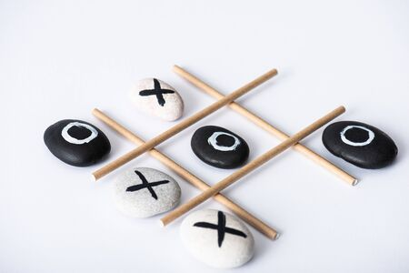 tic tac toe game with grid made of paper tubes, and pebbles marked with naughts and crosses on white surface