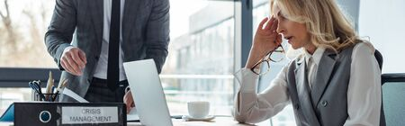 Panoramic shot of businesswoman looking at laptop near folder with crisis management and businessman in office