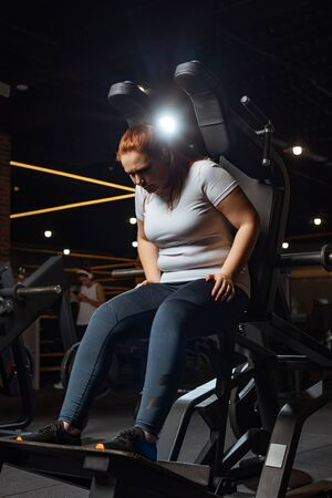 overweight girl in sportswear training on fitness machine in gym