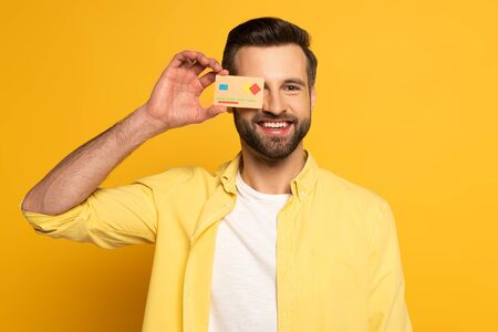 Smiling man covering eye with model of credit card on yellow background