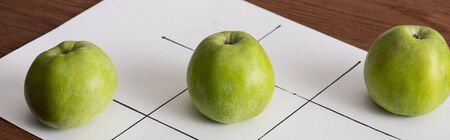 panoramic shote of tic tac toe game on white paper with row of three green apples on wooden surface