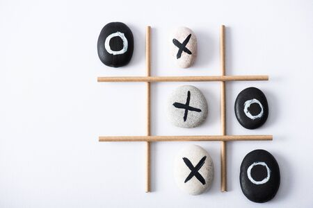 top view of tic tac toe game with grid made of paper tubes, and pebbles marked with crosses and naughts on white surface Stok Fotoğraf
