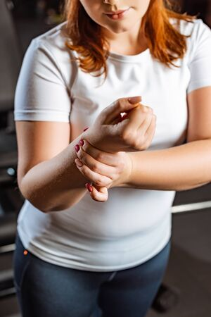 cropped view of overweight girl checking pulse with hand