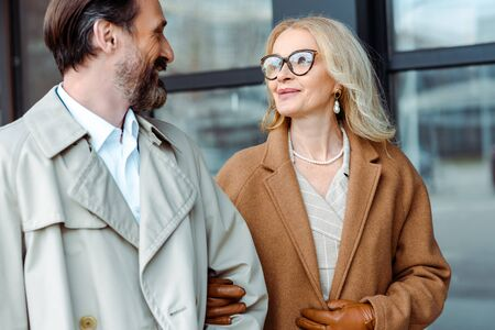 Smiling businesswoman looking at handsome businessman near building on urban street
