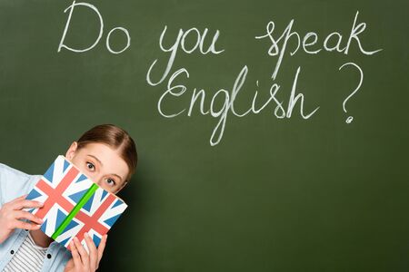 pretty girl with obscure face holding book with uk flag near chalkboard with do you speak English lettering
