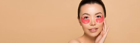 panoramic shot of tender asian woman with pink collagen eye pads isolated on beige