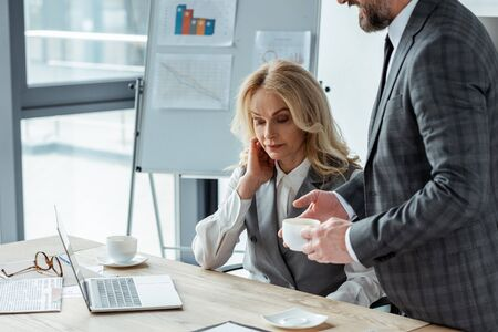 Businessman holding coffee cup near businesswoman and laptop on table in office