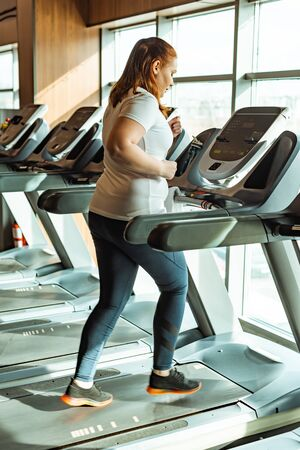 overweight girl working out on treadmill in gym near window Stock Photo