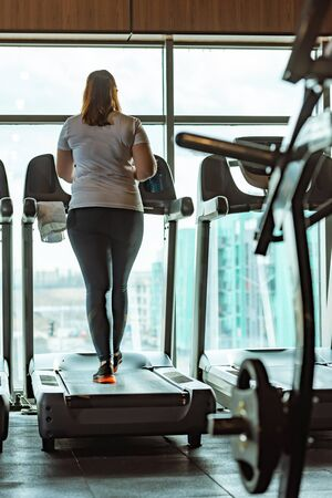 back view of overweight girl running on treadmill in gym against window
