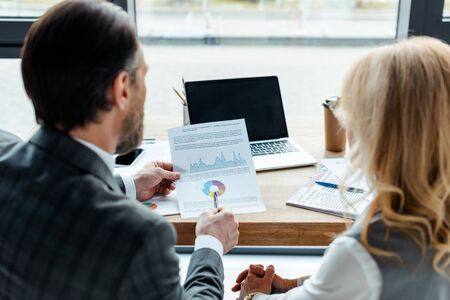 Back view of businessman pointing on charts near businesswoman and devices on table