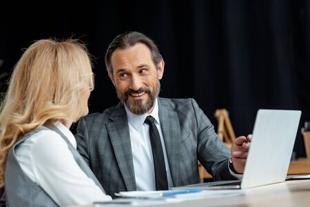 Selective focus of smiling businessman looking at businesswoman near laptop and papers on table