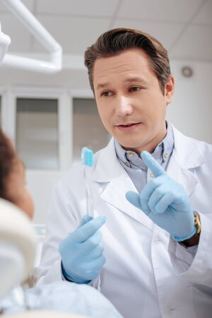selective focus of dentist gesturing near african american woman while holding toothbrush Stockfoto