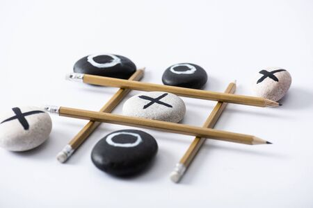 tic tac toe game with grid made of pencils and pebbles marked with naughts and crosses on white surface Stok Fotoğraf