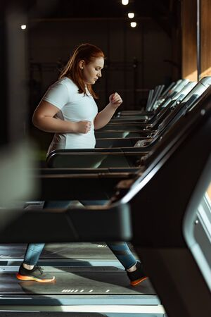 selective focus of focused overweight girl running on treadmill in gym