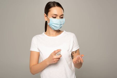 Young woman in medical mask using hand sanitizer isolated on grey