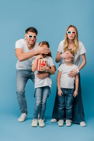 shocked parents in 3d glasses closing eyes to kids holding popcorn bucket on blue