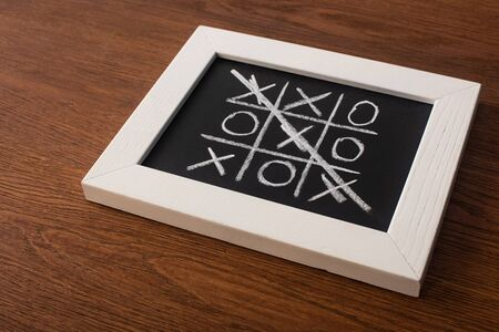 tic tac toe game on blackboard with crossed out row of crosses on wooden surface