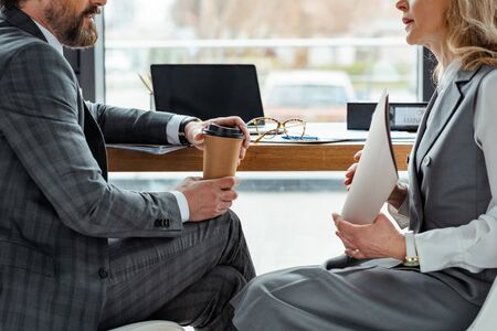 Cropped view of business people with coffee to go and paper folder sitting at table in office