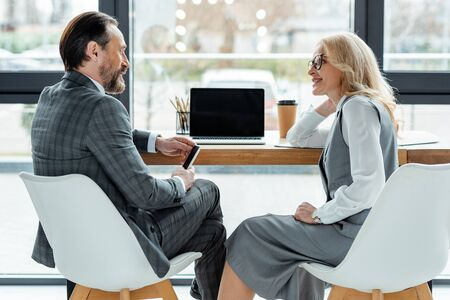 Side view of businesswoman smiling at businessman with smartphone near laptop on table in office