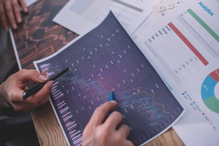 Cropped view of data analysts working with charts and papers on table