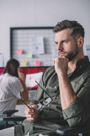 Selective focus of computer systems analyst looking away while colleague working in office