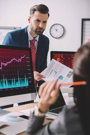 Selective focus of data analyst holding papers with charts and looking at colleague near computers on table