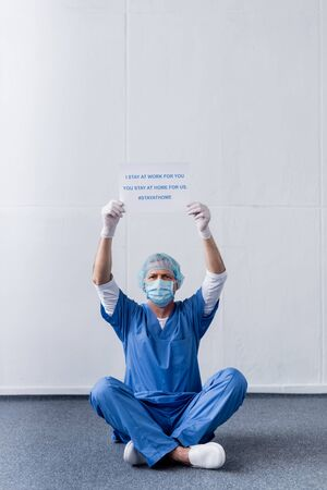 middle aged doctor in medical mask and cap holding placard with i stay at work for you, you stay at home for us lettering while sitting on white Foto de archivo