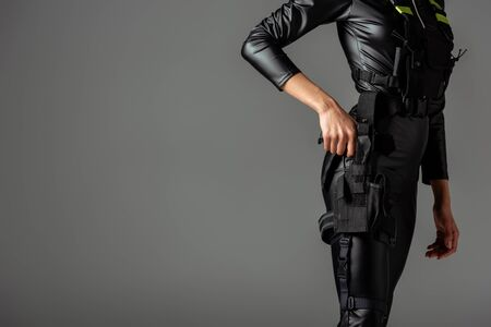 cropped view of futuristic african american woman in glasses with gun on grey 免版税图像