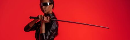 attractive futuristic african american woman in glasses with sword isolated on red, panoramic shot