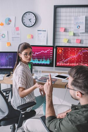 Selective focus of data analysts planning work near charts on computer monitors