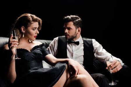 homme et femme élégants assis sur un canapé en cuir avec des verres de champagne et se regardant isolés sur fond noir Banque d'images