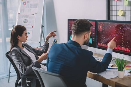 Data analysts pointing on charts on computer monitors while testing security software in office