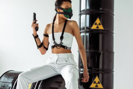futuristic african american woman in safety mask with gun near radioactive waste barrels on white background