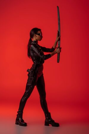 side view of futuristic african american woman in glasses with sword on red background