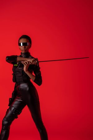 attractive futuristic african american woman in glasses with sword isolated on red background