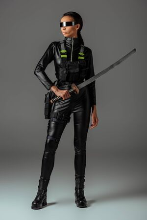 attractive futuristic african american woman in glasses with sword on grey