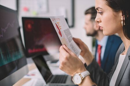 Selective focus of data analyst looking at charts on paper while working with colleague in office