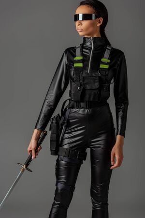 attractive futuristic african american woman in glasses with sword isolated on grey