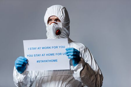 mature doctor in hazmat suit holding placard with i stay at work for you, you stay at home for us lettering isolated on grey Foto de archivo