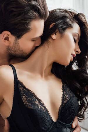 Man hugging and kissing hot girl with closed eyes